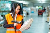 Logistics - female worker or shipper with protective vest and scanner, scans bar-code of package, he