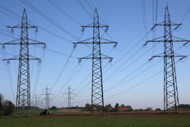 picture of power lines  - power lines and tractor in clear blue sky