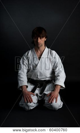 Man In A Kimono With A Black Belt Meditates On A Black Background