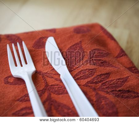 Plastic knife and fork on orange cloth napkin on kitchen table