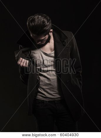 young fashion man checking his coat for the price tag on dark studio background