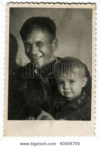 MOSCOW, USSR - CIRCA 1940s : An antique photo shows Smiling Red Army officer and his little son.