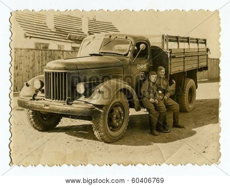 MOSCOW, USSR - CIRCA 1960s : An antique photo shows two Red Army soldiers near a military truck ZIL.