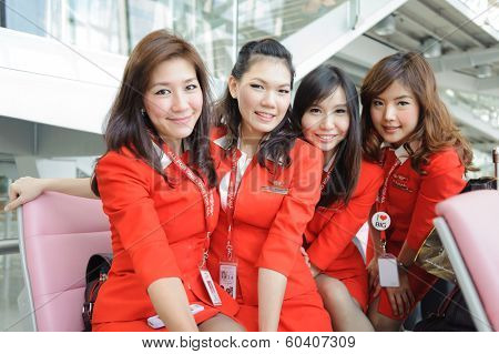 BANGKOK - OCT 27: Airasia crew members posing in Bangkok Airport on October 27, 2011 in Bangkok, Thailand. AirAsia Berhad is a Malaysian low-cost airline headquartered in Kuala Lumpur, Malaysia