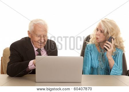 Elderly Couple Her On Phone Him Computer