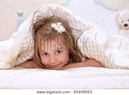 Sweet little girl lying down in the bed covered with blanket, cute flower in hair, sleeping in child bedroom, happy childhood concept
