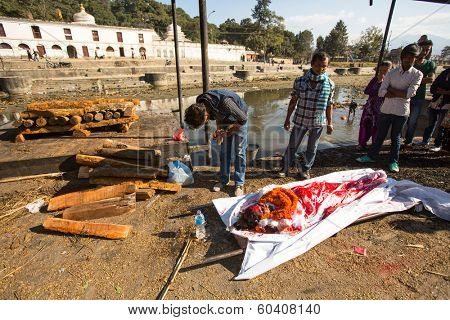 KATHMANDU, NEPAL - DEC 3: Unidentified local people during the cremation ceremony along the holy Bagmati River in Bhasmeshvar Ghat at Pashupatinath temple, Dec 3, 2013 in Kathmandu, Nepal.