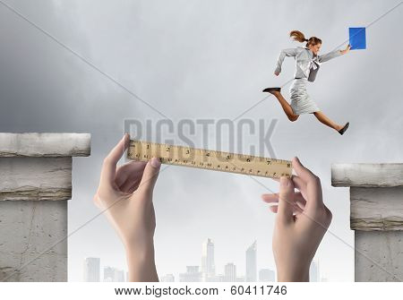 Young businesswoman jumping over gap. Risk concept