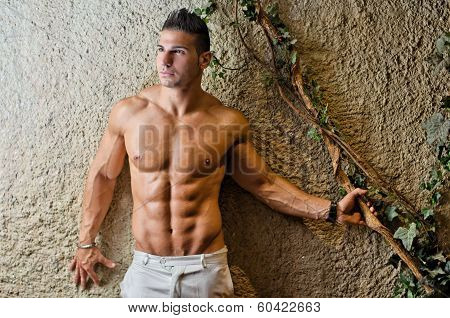Muscular Young Latino Man Shirtless In White Pants Leaning On Wall