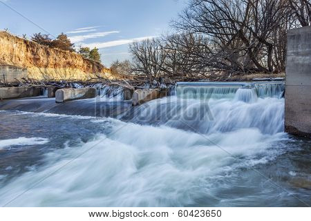 river dam diverting water for farmland irrigation, Cache la Poudre RIver in Fort Collins, Colorado, winter or early spring scenery