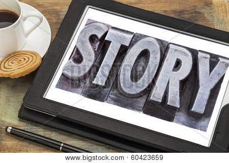 story  - a word in grunge letterpress metal type on a  digital tablet with a cup of coffee
