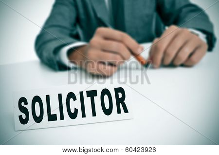 a man wearing a suit sitting in a desk with a desktop nameplate in front of him with the word solicitor