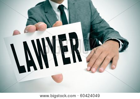 a man wearing a suit sitting in a desk holding a signboard with the word lawyer written in it
