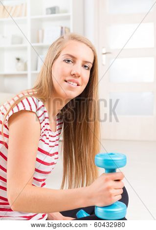 Beautiful young woman with dumb bells resting after exercises at her home.