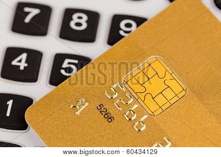 a gold credit card and a calculator. symbolic photo for cashless purchases and status symbols.