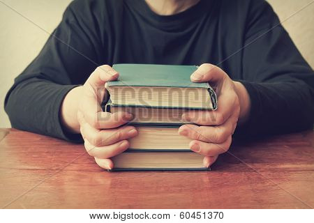 Woman Sitting At The Table And Keeps A Stack Of Old Books