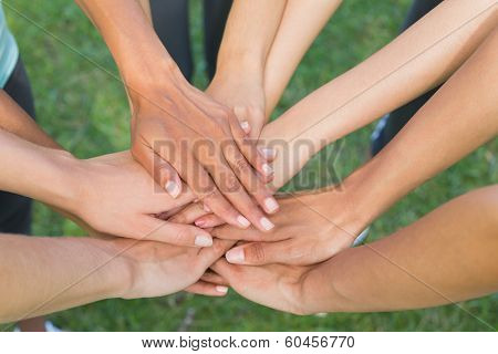 Closeup of human hands stacked upon one another in the park