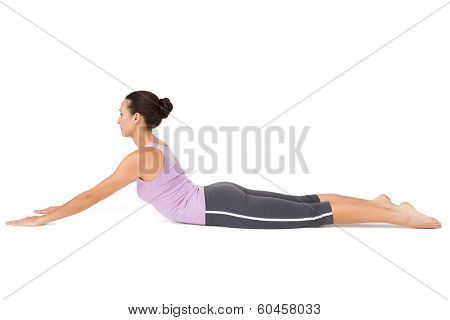 Full length side view of a fit young woman doing the cobra pose over white background