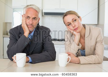 Bored business couple having coffee before work in morning at home in the kitchen
