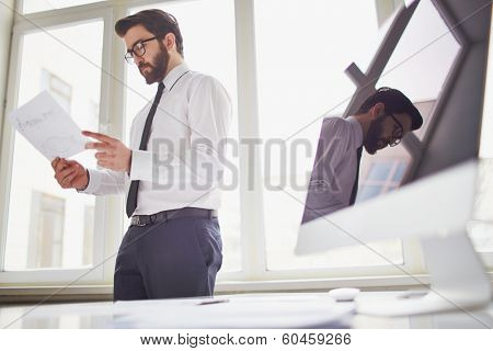Young businessman standing by the window in office and looking at paper