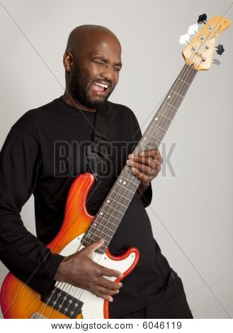 Man playing bass guitar enthusiastically