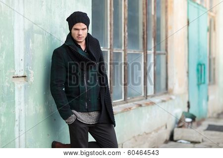 young fashion man posing outdoor, by an old building, with his hands in his pockets and a foot on the wall while looking into the camera