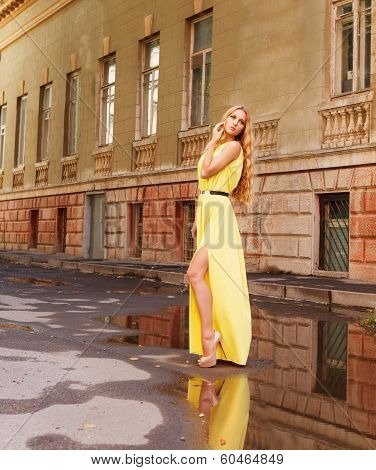 Beautiful Blond Woman In Long Yellow Dress Outdoors