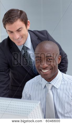 Smiling Businesmen Working Together With A Computer