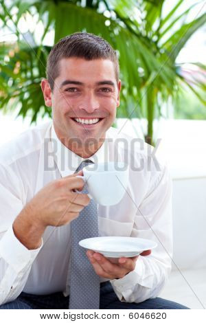 Businessman Drinking A Cup Of Coffee On A Sofa In Workplace