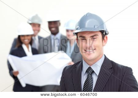 Attractive Male Architect With His Team In The Background