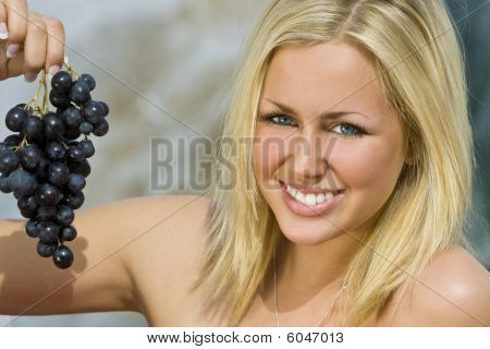 Beautiful Young Blond Woman Eating A Bunch Of Grapes