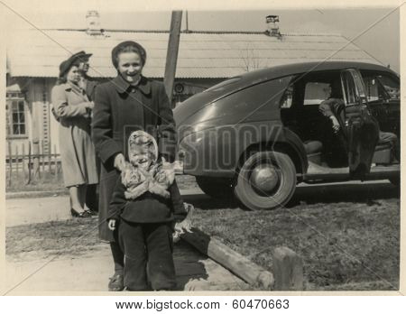 MOSCOW, USSR - CIRCA 1960s : An antique photo shows Soviet family and their car.