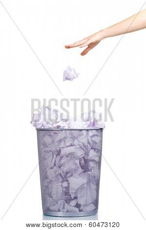 Metal trash bin from paper and hand isolated on white