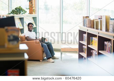 Full length portrait of smiling student reading book in bookstore