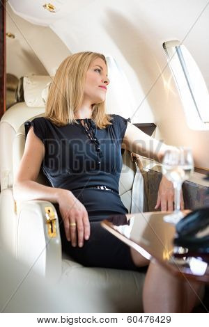 Beautiful rich woman looking through window in private jet