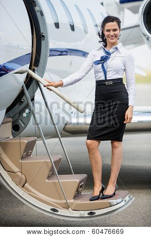 Full length portrait of young stewardess standing on ladder of private jet