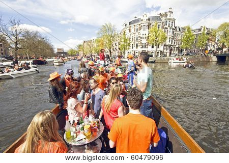 AMSTERDAM, HOLLAND - APRIL 30, 2013: Amsterdam canals full of boats and people in orange during the celebration of queensday