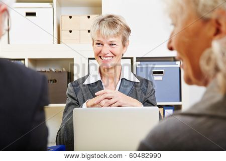 Senior couple getting financial advice from woman in a bank