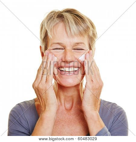 Elderly attractive woman caressing her skin with lotion