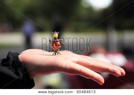Jewelry miniature of russian samovar on the hand