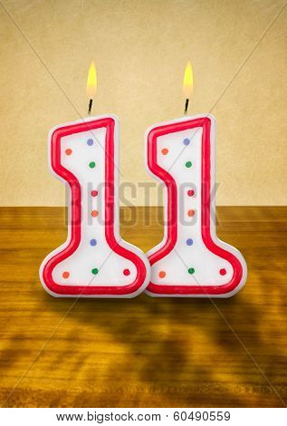 Burning birthday candles number 11 on a wooden background
