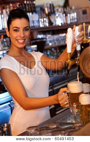 Portrait of attractive female bartender tapping beer in pub, looking at camera, smiling.