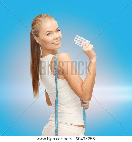 fitness, health, pharmacy and diet concept - sporty woman with measuring tape and diet pills