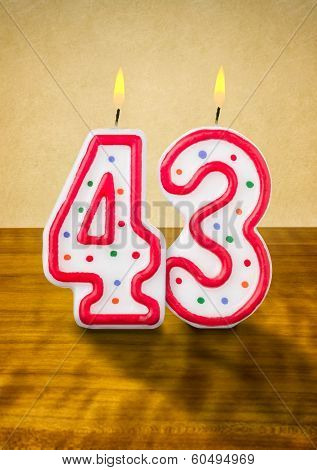 Burning birthday candles number 43 on a wooden background