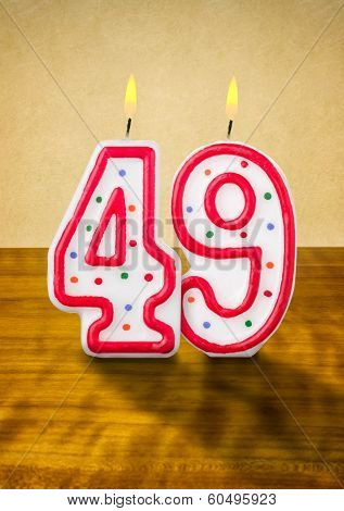 Burning birthday candles number 49 on a wooden background