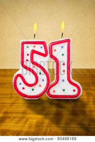 Burning birthday candles number 51 on a wooden background