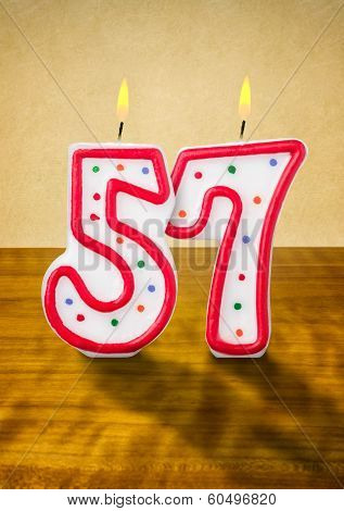 Burning birthday candles number 57 on a wooden background
