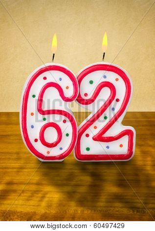 Burning birthday candles number 62 on a wooden background