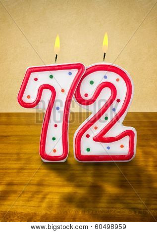 Burning birthday candles number 72 on a wooden background
