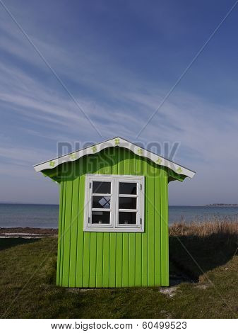 Bright green beach hut on the Danish island of Aero with background of sea and blue sky